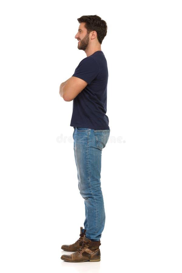 Молодой человек в джинсах и голубой футболке стоит с пересеченными оружиями и смотрит прочь r стоковые фотографии rf