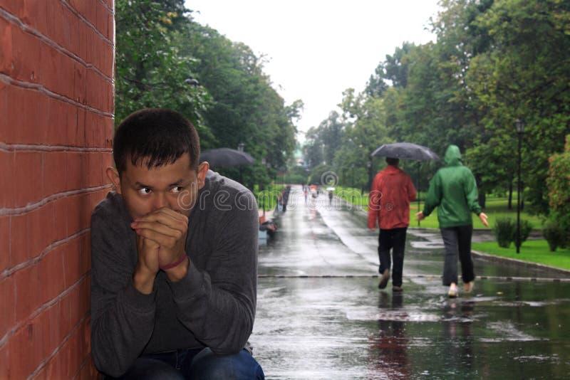 Молодой человек в идя дождь дне стоковые изображения