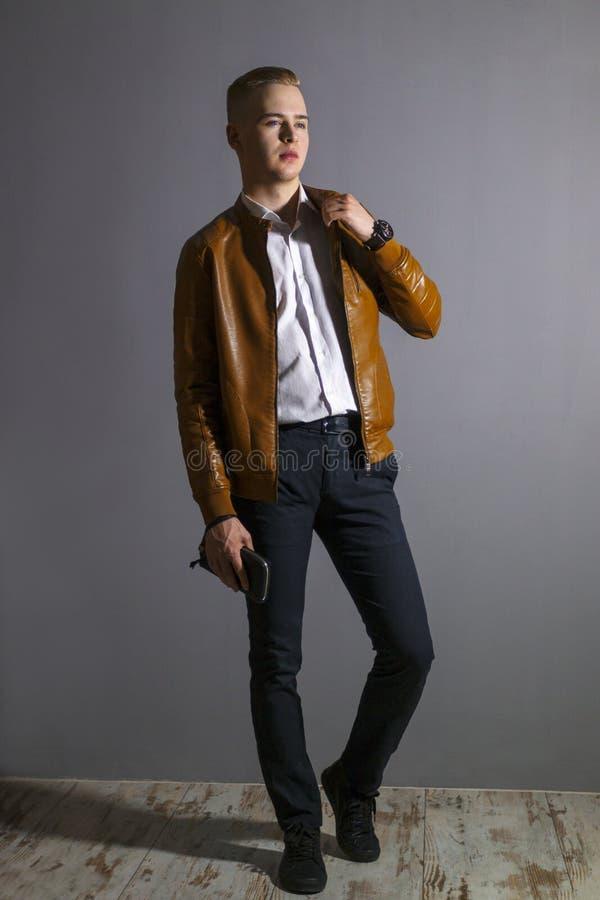 Молодой человек в кожаной куртке представляет с портмонем стоковые фото