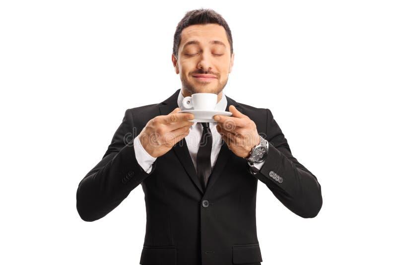 Молодой человек в костюме наслаждаясь запахом кофе стоковая фотография rf