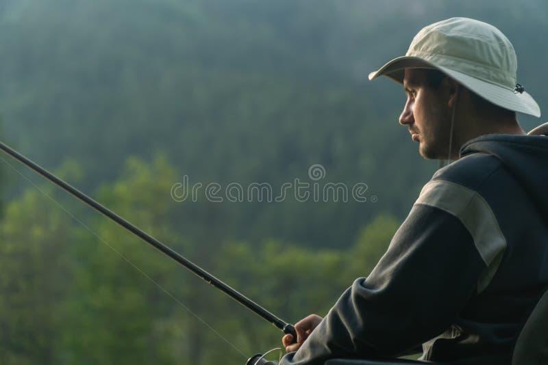 Молодой человек в кресло-коляске удя на красивом озере в заходе солнца, рассвете стоковое изображение rf
