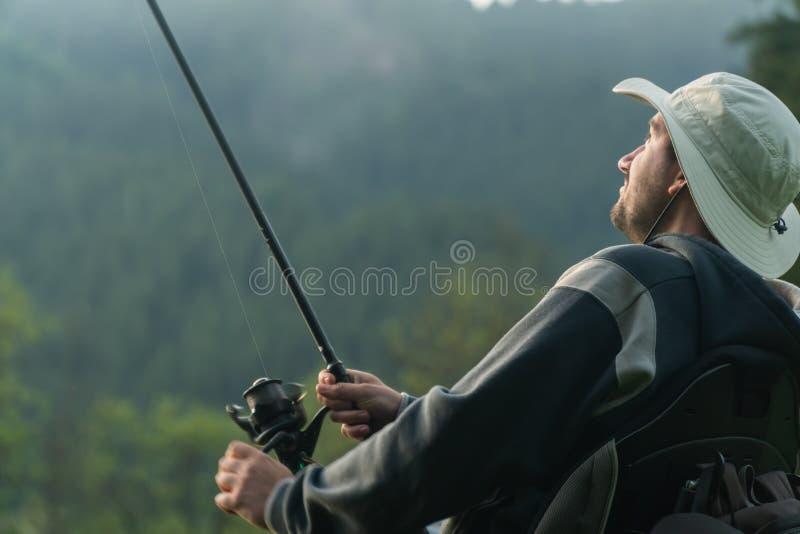 Молодой человек в кресло-коляске удя на красивом озере в заходе солнца, рассвете Смотрящ рыб которые он уловил стоковые изображения rf