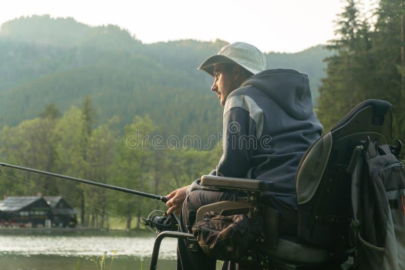 Молодой человек в кресло-коляске удя на красивом озере в заходе солнца, рассвете стоковое изображение