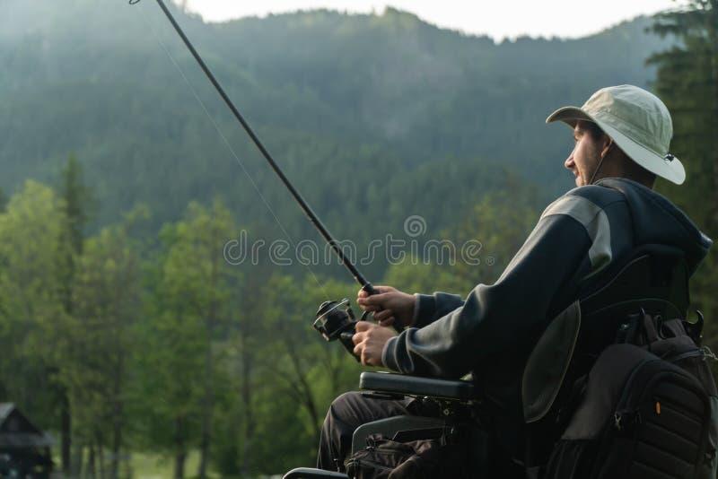 Молодой человек в кресло-коляске удя на красивом озере в заходе солнца, рассвете стоковая фотография