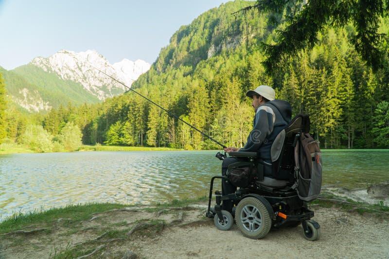 Молодой человек в кресло-коляске удя на красивом озере на солнечный день, с горами в задней части стоковое фото