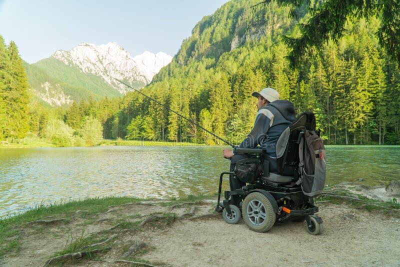 Молодой человек в кресло-коляске удя на красивом озере на солнечный день, с горами в задней части стоковые изображения rf