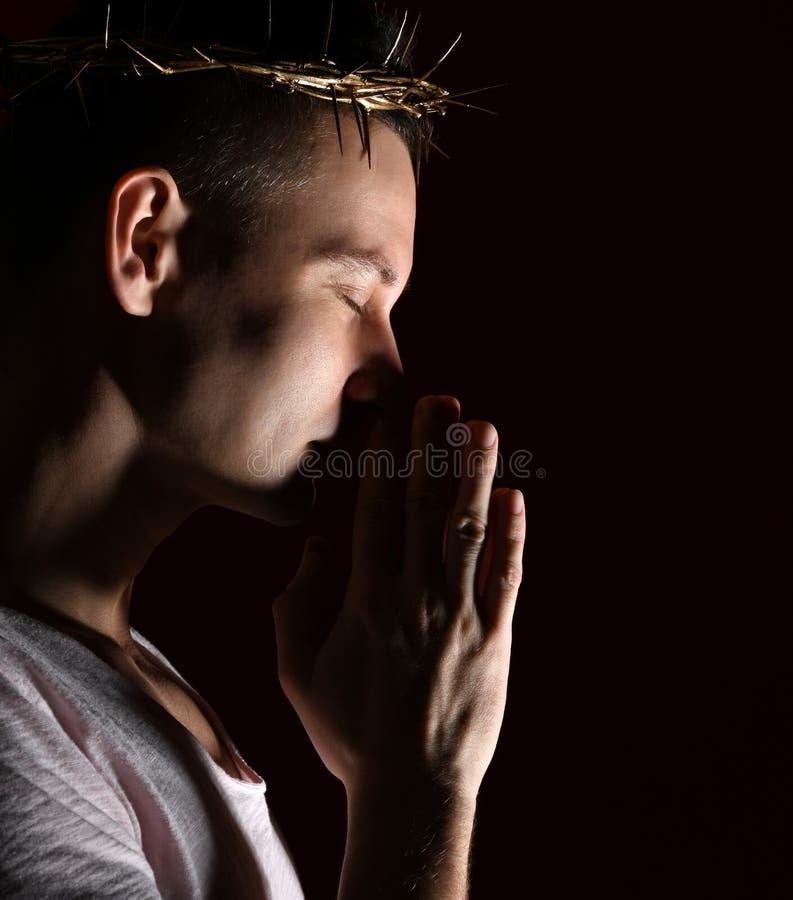 Молодой человек в кроне терниев, мученик с закрытыми eys imploringly сжимал его съемку рук бортовую стоковое фото