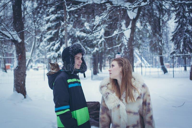 Молодой человек в меховой шапке с earflap с котенком в клобуке его куртки и девушки в бежевой меховой шыбе против стоковая фотография rf