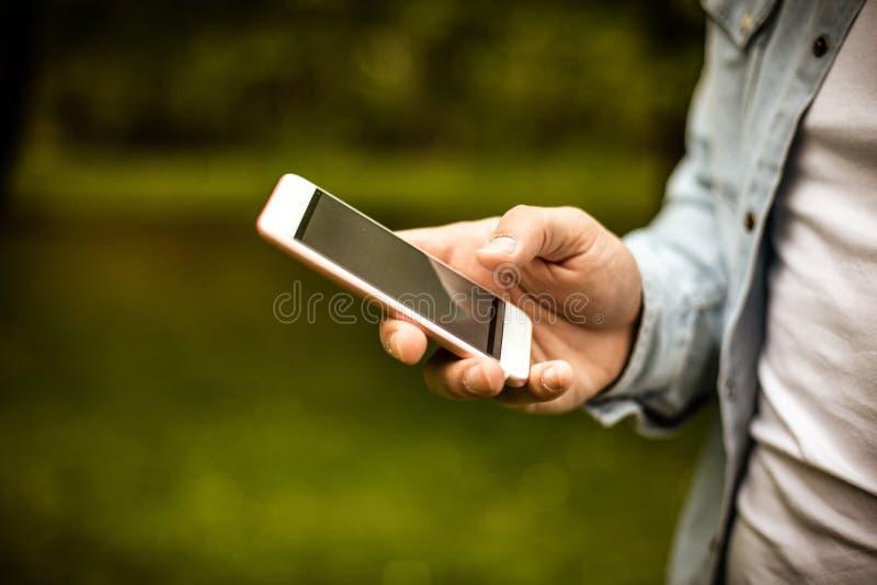 Молодой человек в парке используя мобильный телефон стоковые изображения rf