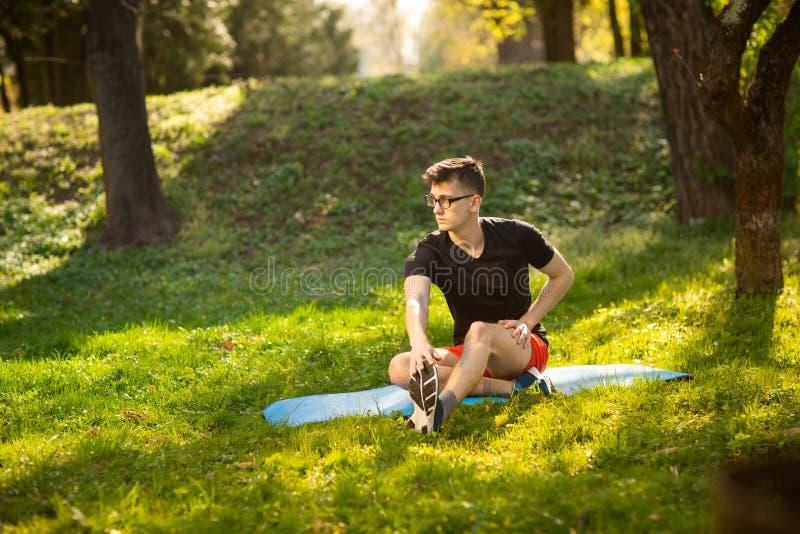 Молодой человек в стеклах тренируя йогу outdoors Sporty парень делает ослабляя тренировку на голубой циновке йоги, в парке r стоковые изображения