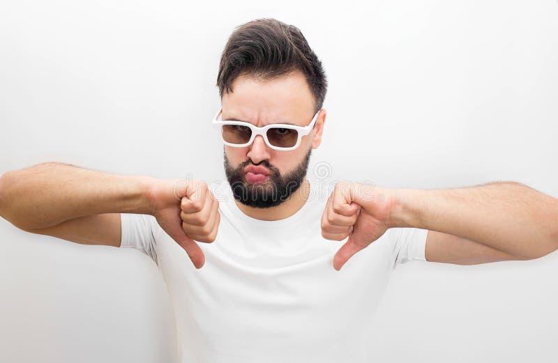 Молодой человек в стеклах фильма стоять и держать его большие большие пальцы руки вниз Он невзлюбит фильм Гай несчастно Молодой ч стоковое фото rf
