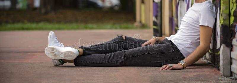Молодой человек в туфлях 'Адидас Стэн Смит' на улице стоковые изображения