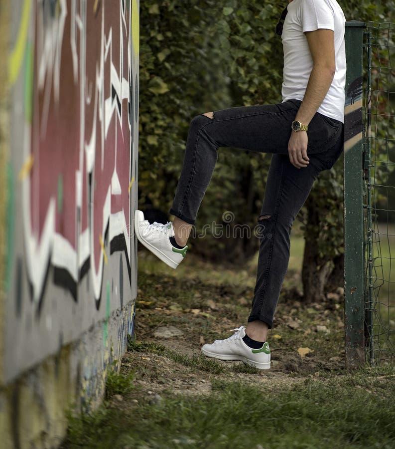 Молодой человек в туфлях 'Адидас Стэн Смит' на улице стоковые изображения rf