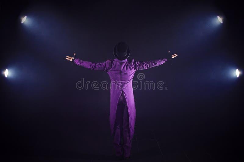 Молодой человек в фиолетовом костюме стоя на предпосылке фары Showman распространяя руки, выставку начинает стоковые фотографии rf