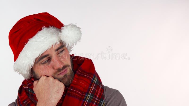 Молодой человек в шляпе Санта рождества выглядя расстроенный стоковое изображение