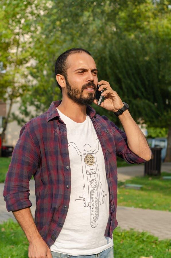 Молодой человек говорит на его сотовом телефоне на парке стоковые изображения