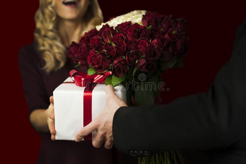Молодой человек дает подарку белую коробку с красным смычком и цветки девушке на изолированной черной предпосылке Принципиальная  стоковые фотографии rf