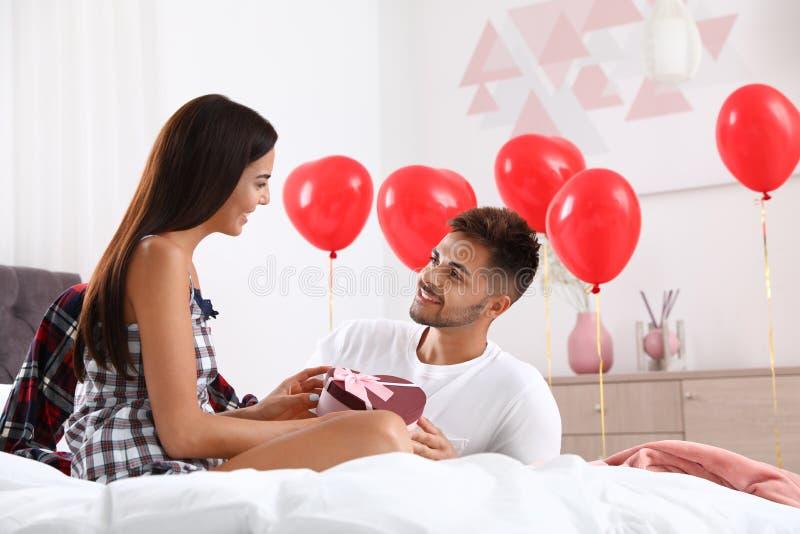Молодой человек дарит подарок своей девушке в спальне Празднование Дня Святого Валентина стоковые фото