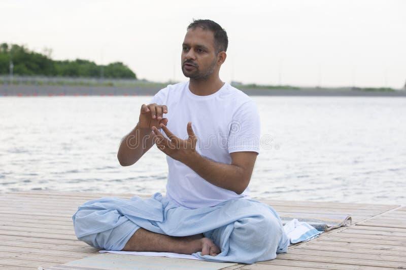 Молодой человек делая йогу в парке утра человек ослабляет в природе стоковая фотография rf