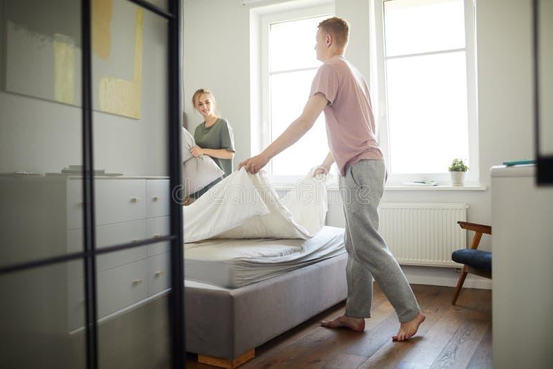 Молодой человек делая кровать пока помогающ его жене в утре стоковые изображения