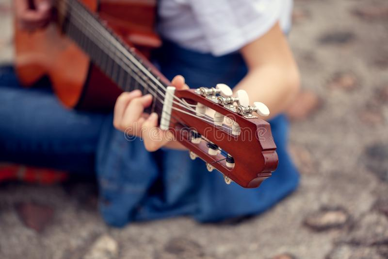 Молодой человек держа гитару и играя музыку Фокус на голове гитары 6-строки стоковая фотография