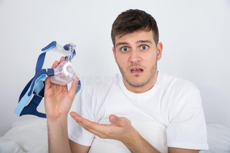 Молодой человек держа машину CPAP стоковая фотография