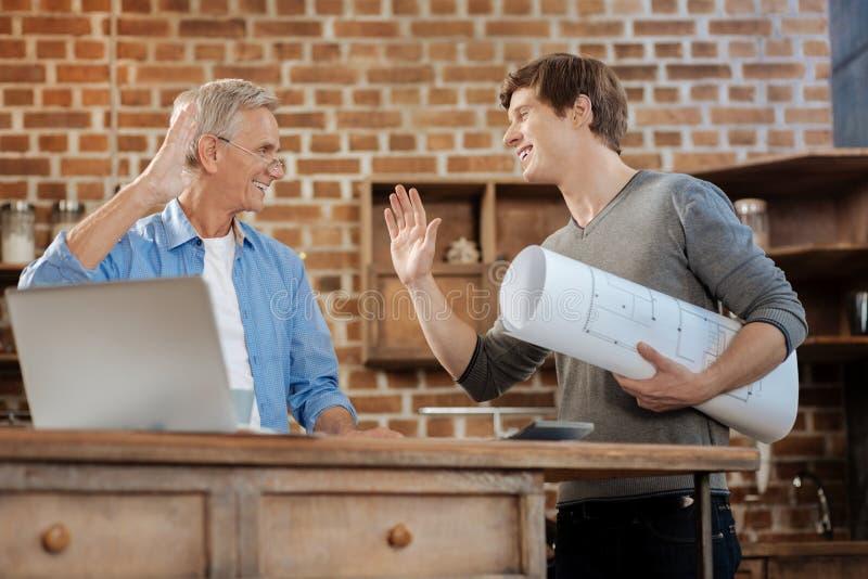 Молодой человек держа светокопию и высоко--fiving его ментор стоковые фотографии rf