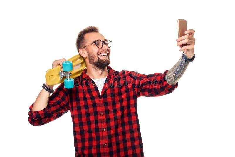 Молодой человек держа скейтборд на плече поднимая его телефон принимает selfie на белой предпосылке стоковое фото