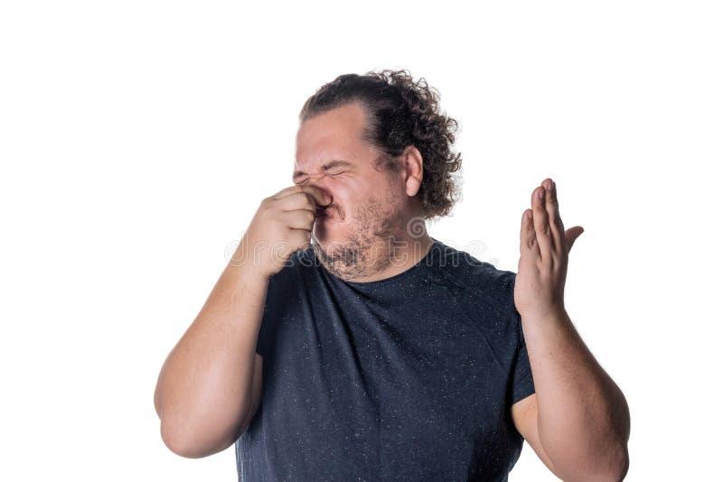 Молодой человек держит или сжимает его нос закрытый из-за вонючих запаха или запаха белизна изолированная предпосылкой стоковые фото