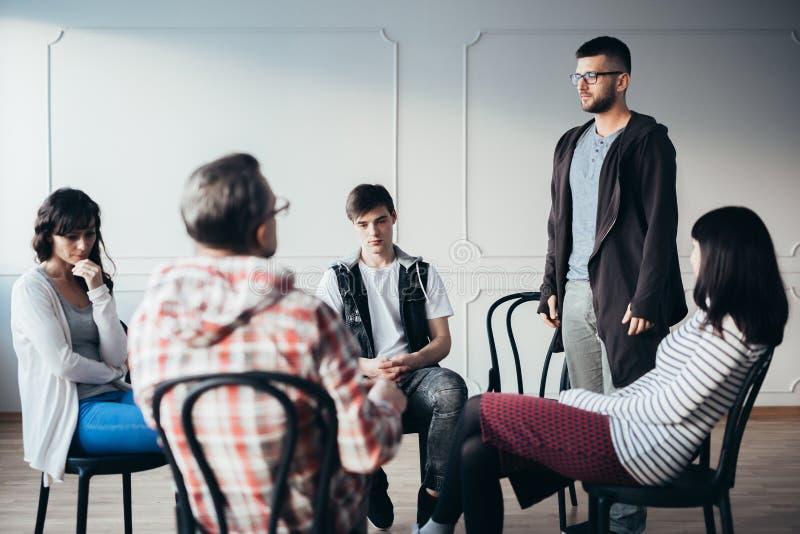 Молодой человек допуская что он алкоголичка во время групповой встречи группы поддержки стоковая фотография rf
