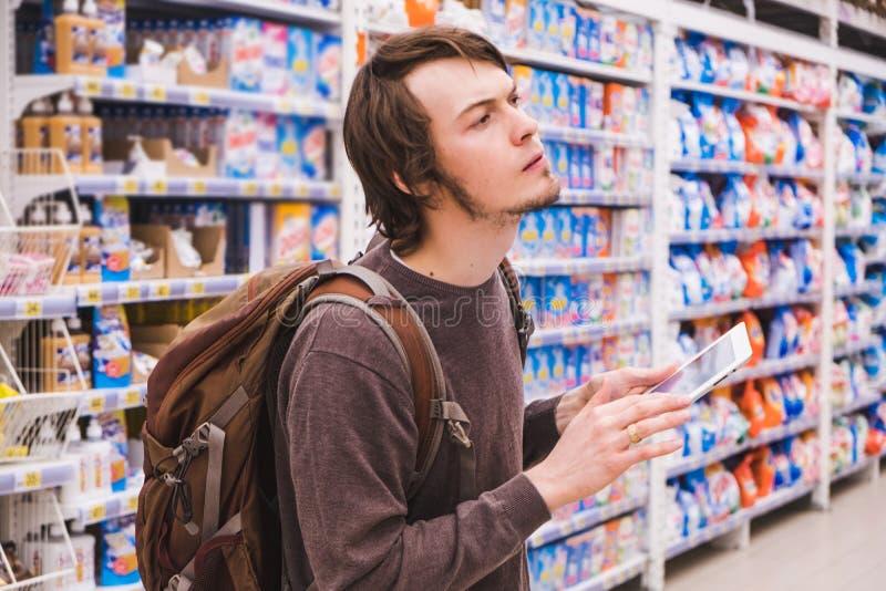 Молодой человек думает о покупках с таблеткой выбирает химикаты домочадца в супермаркете стоковые изображения