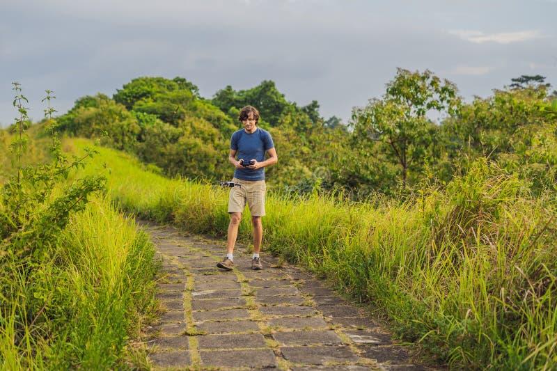 Молодой человек запускает трутня в небо Остров Бали стоковое фото rf