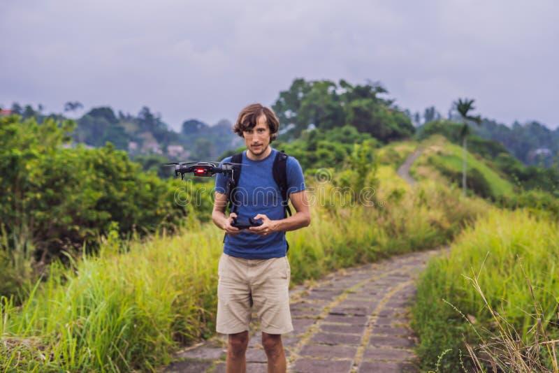 Молодой человек запускает трутня в небо Остров Бали стоковое изображение
