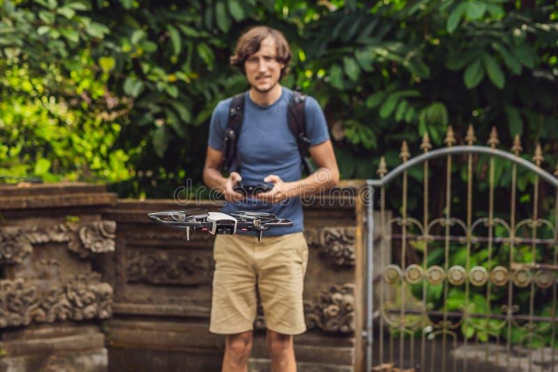 Молодой человек запускает трутня в небо Остров Бали стоковые изображения