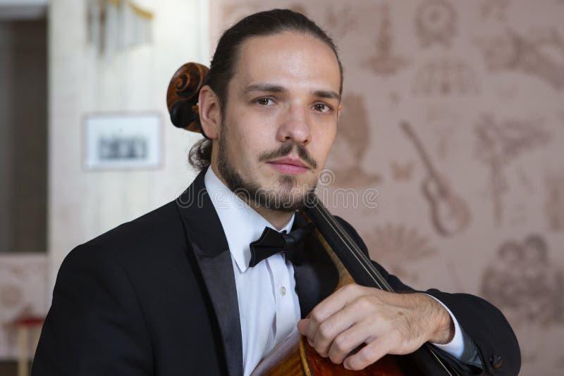 Молодой человек играя виолончель Портрет виолончелиста стоковое изображение rf
