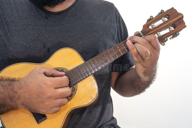 Молодой человек играя гавайскую гитару с рубашкой и черными брюками стоковое изображение rf