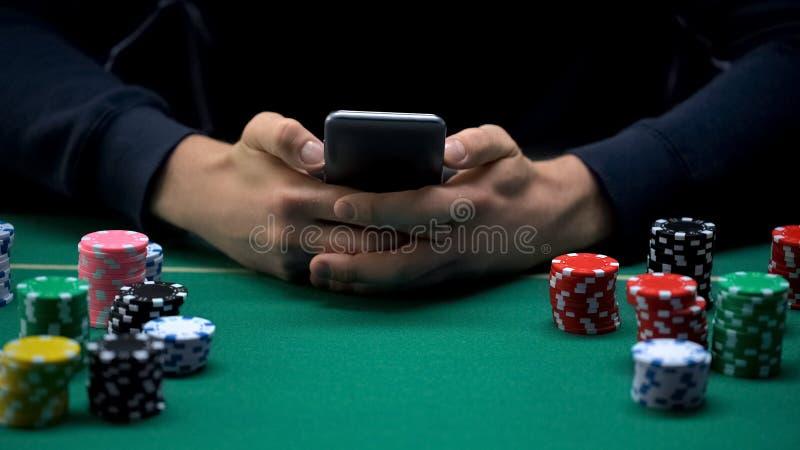 Молодой человек играя игры азартных игр на приложении мобильного телефона, вебсайте казино стоковые изображения rf