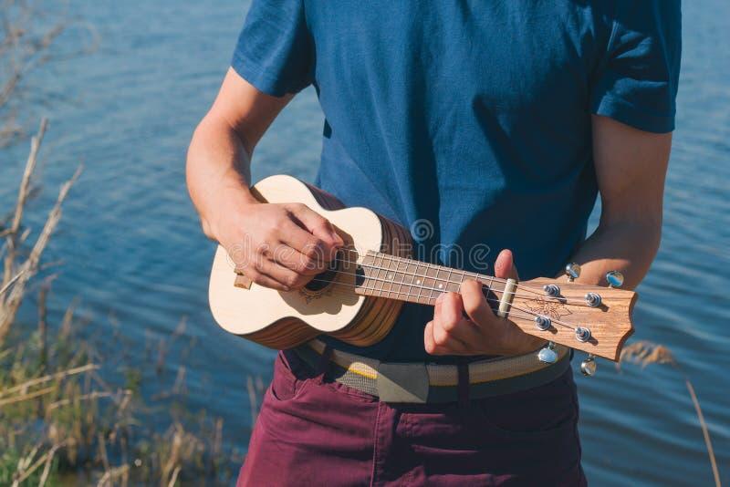 молодой человек играя на гавайской гитаре на предпосылке озера на солнечный летний день стоковое фото rf
