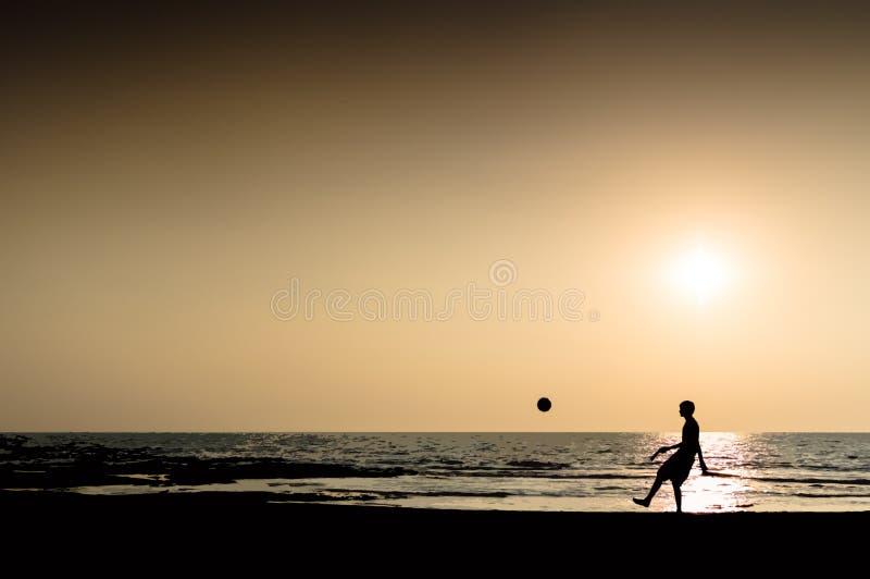 Молодой человек играя horiz захода солнца горизонта океана силуэта футбола стоковое фото