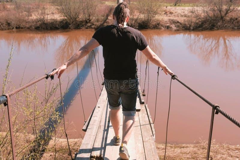 Молодой человек идет на приостанавливанный деревянный мост над рекой задний взгляд стоковые изображения rf