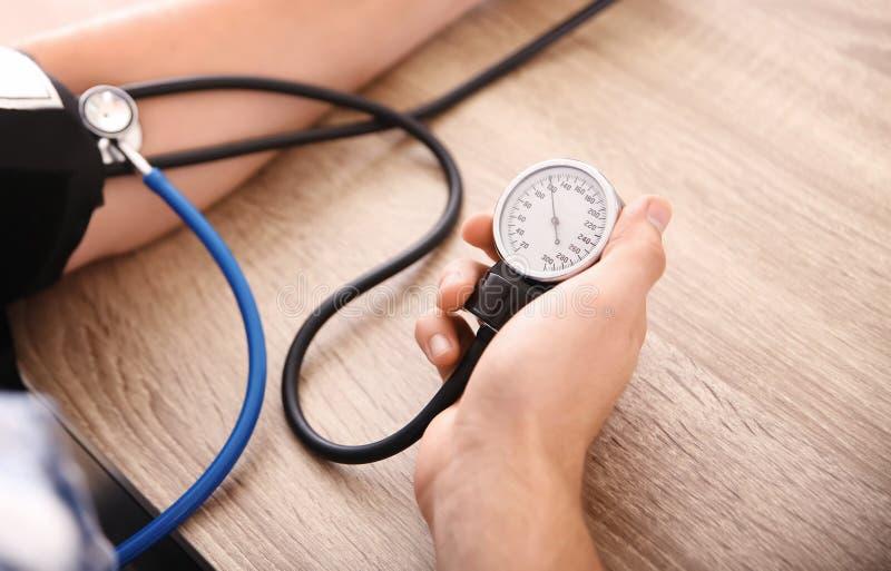 Молодой человек измеряя его кровяное давление дома стоковое фото rf