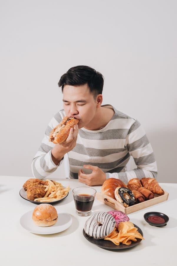 Молодой человек имеет завтрак фаст-фуда стоковые изображения
