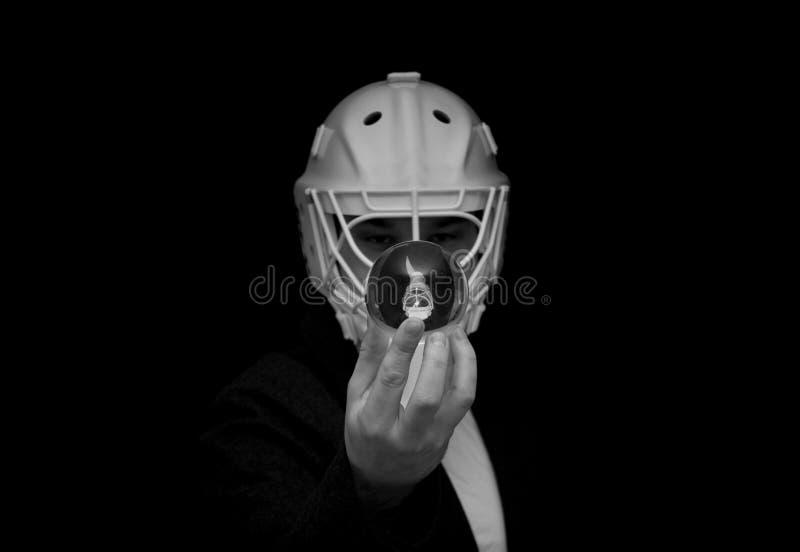 Молодой человек имеет шлем вратаря на его голове и держит хрустальный шар с его отражением стоковые изображения rf