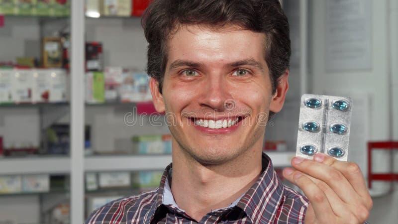 Молодой человек имея головную боль держа пилюльки стоковое фото