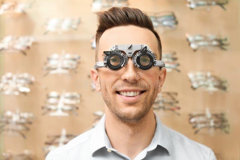 Молодой человек имея рассмотрение глаза с phoropter стоковая фотография rf