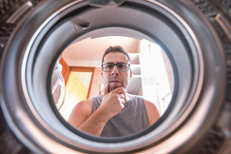 Молодой человек интересуя как стиральная машина работает стоковые фотографии rf