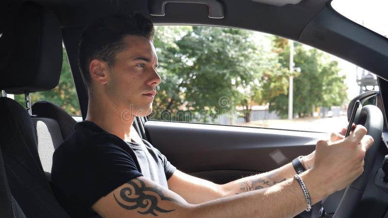 Молодой человек используя его сотовый телефон управляя автомобилем стоковое изображение