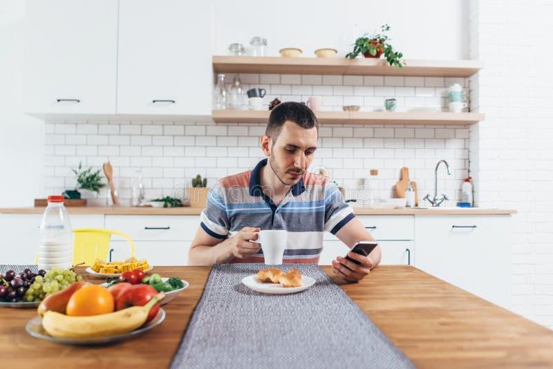 Молодой человек используя его smartphone пока имеющ завтрак дома стоковое фото