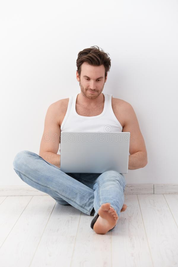 Молодой человек используя компьтер-книжку на усмехаться пола стоковое изображение rf