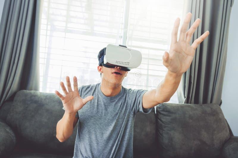 Молодой человек используя стекла виртуальной реальности имея потеху с имитатором VR дома стоковые фото